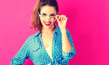 smile face: Happy young woman on a pink background
