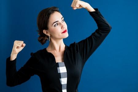 濃い青の背景に強力な若い女性 写真素材