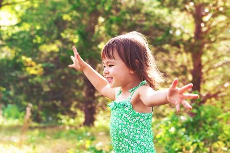 Gelukkig lachend peuter meisje buiten spelen