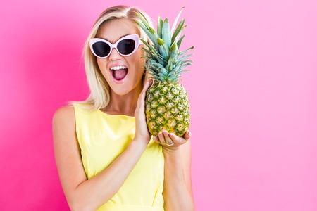 Glückliche junge Frau, die eine Ananas auf einem rosa Hintergrund Standard-Bild - 65973253