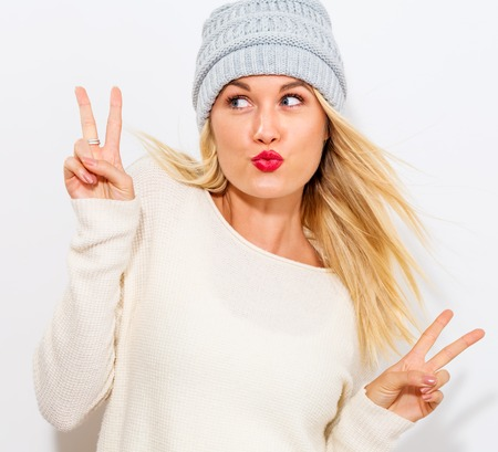 Young woman giving the peace sign on a white background Stock Photo