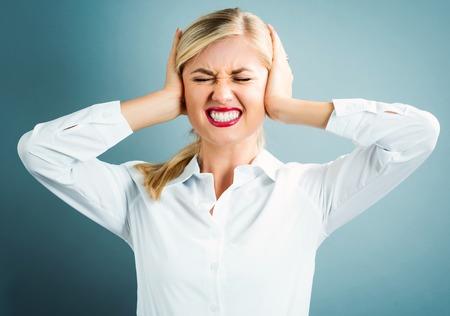 ruido: Mujer joven bloqueo de las orejas sobre un fondo gris