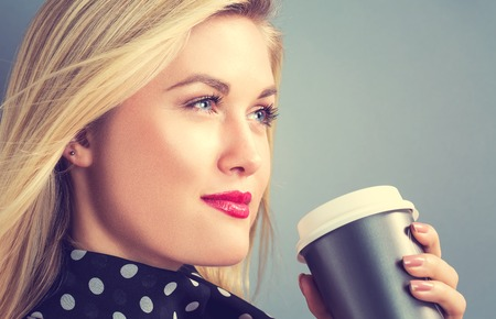 tomando café: Young blonde woman drinking coffee on a gray background Foto de archivo