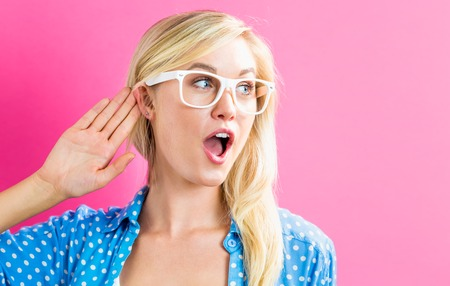escuchar: Young blonde woman listening on a pink background