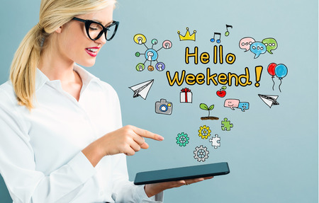 Hello Weekend text with business woman using a tablet Stock Photo