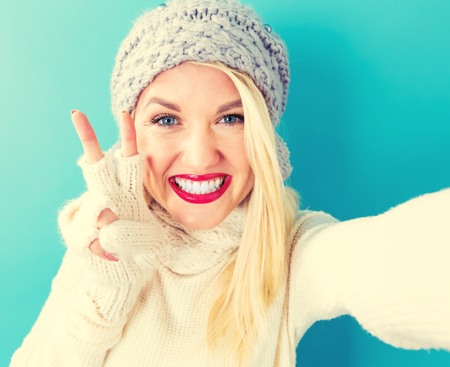 background color: Young woman in winter clothes taking a selfie