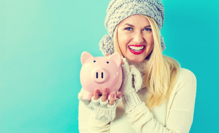 christmas savings: Young woman with a piggy bank on a blue background