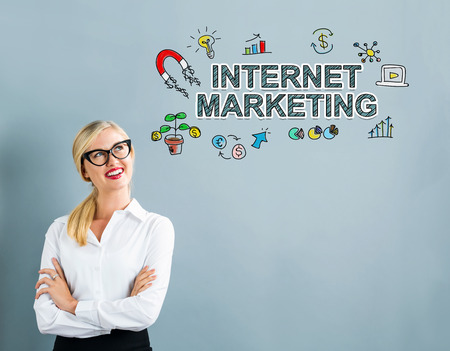 internet marketing: Internet Marketing text with business woman on a gray background Stock Photo