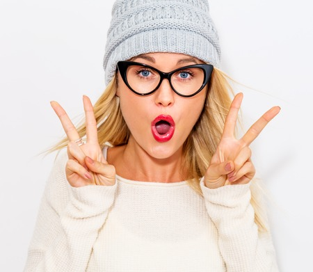 one people: Young woman giving the peace sign on a white background Stock Photo
