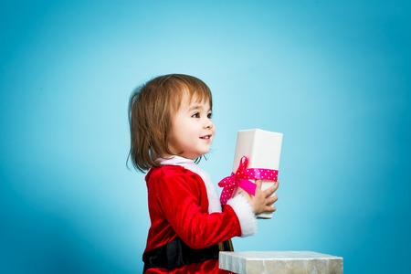 happy christmas: Happy toddler girl in a Santa costume with a gift box