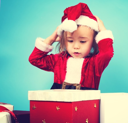 Happy toddler girl in a Santa costume with gift boxes Stock Photo