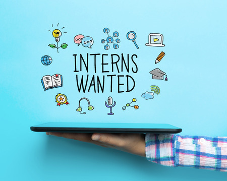 tablet pc in hand: Interns Wanted concept with a tablet on blue background Stock Photo