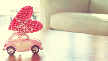 miniature: Miniature pink car carrying a big red heart cushion Stock Photo