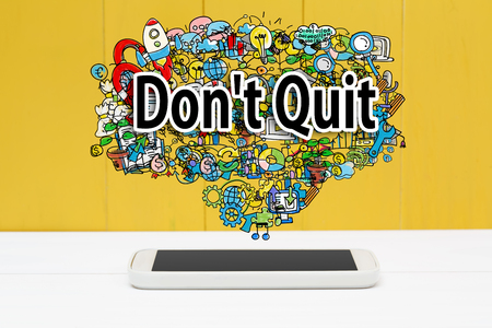 quit: Dont Quit concept with smartphone on yellow wooden background