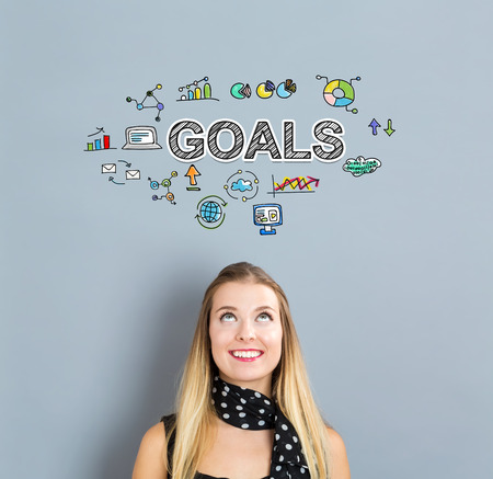 Goals concept with happy young woman on a gray background Stock Photo