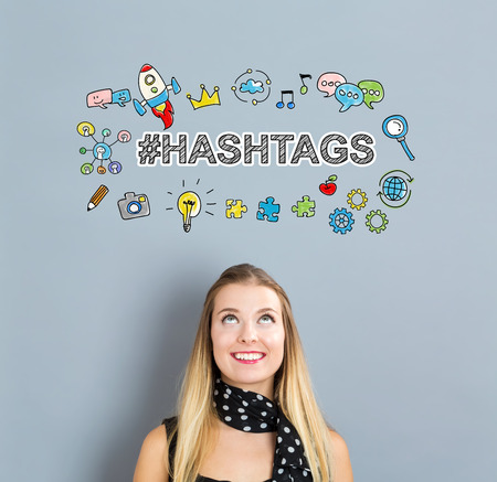 Hashtags concept with happy young woman on a gray background Stock Photo