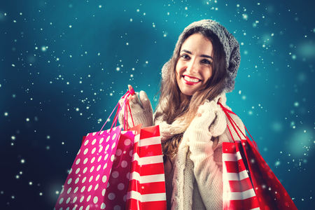 white winter: Happy young woman holding shopping bags in snowy night Stock Photo
