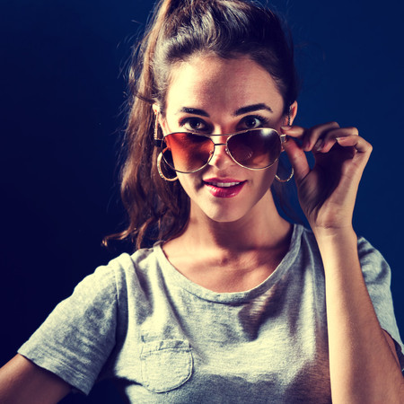 young woman smiling: Young woman with sunglasses on a dark blue background Stock Photo