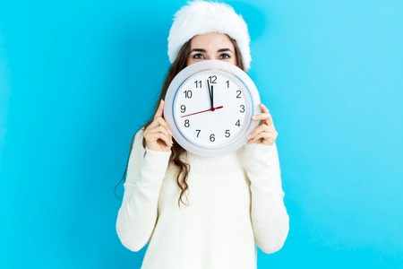 noon: Young woman holding a clock showing nearly 12 Stock Photo
