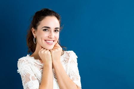 Mujer joven feliz sobre un fondo azul Foto de archivo - 68190129