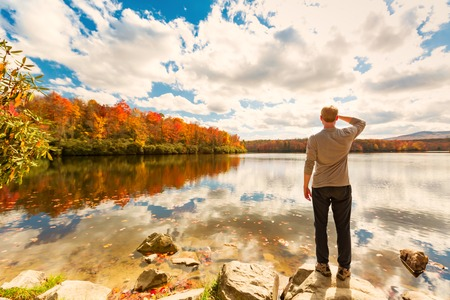 Blue Ridge Mountains: Man standing at he edge of a lake in autumn