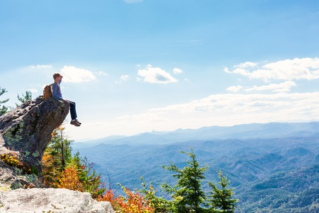cliff edge: Man at the edge of a cliff high above the mountains