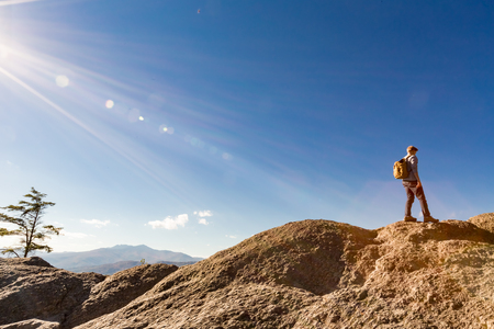 cliff edge: Man walking on the edge of a cliff high above the mountains Stock Photo