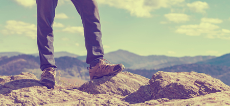 edge: Man at the edge of a cliff high above the mountains