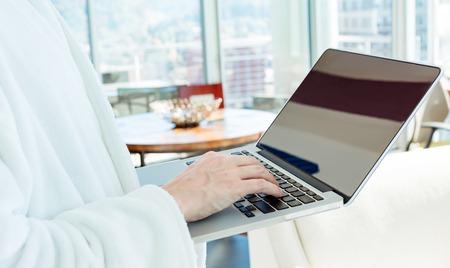 Homme dans un peignoir sur un ordinateur portable dans une fenêtre éclairée Chambre éclairée Banque d'images - 68191737