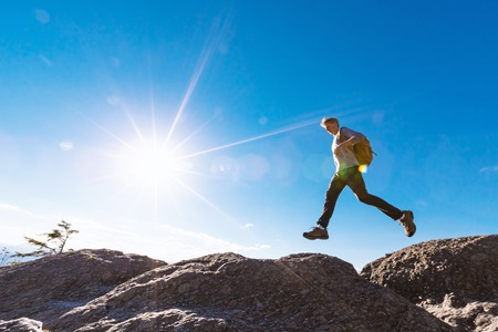 Man jumping over a gap high up on a mountain hike Stock Photo