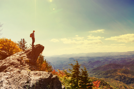 Man walking on the edge of a cliff high above the mountains Stock Photo