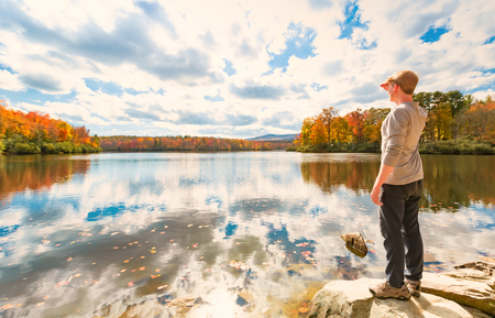 overlook: Man standing at he edge of a lake in autumn