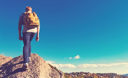 Man walking on the edge of a cliff high above the mountains Reklamní fotografie