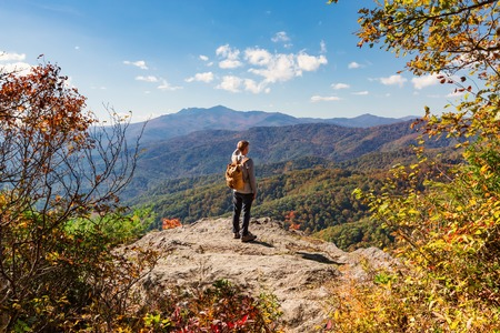 Blue Ridge Mountains: Man walking on the edge of a cliff high above the mountains Stock Photo