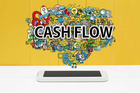 Cash Flow concept with smartphone on yellow wooden background