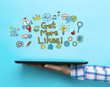 likes: Get More Likes concept with a tablet on blue background Stock Photo