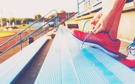 lacing sneakers: Female runner lacing her sneakers on in the bleachers of a stadium Stock Photo