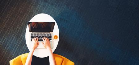 현대 방에서 랩톱 컴퓨터에서 작업하는 사람