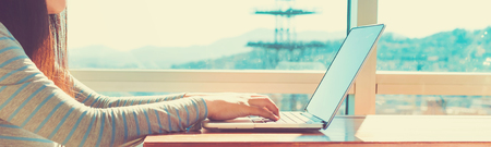 Femme travaillant sur un ordinateur portable dans la chambre éclairée Banque d'images - 68193765