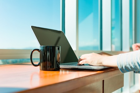 input device: Woman working on a laptop in brightly lit room