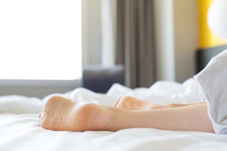 Feet of unidentifiable person sticking out from blanket in morning wake up scene Stock Photo