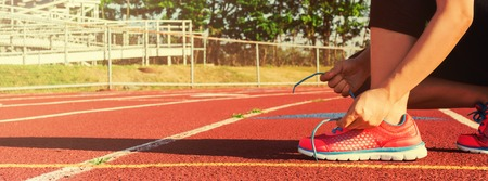 lacing sneakers: Female runner lacing her sneakers on a stadium running track Stock Photo