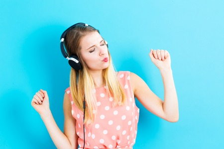 Happy young woman with headphones on a blue background Stock fotó