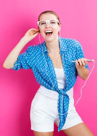 ピンクの背景のイヤホンを持つ幸せな若い女性 写真素材