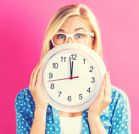 second meal: Young woman holding a clock showing nearly 12 Stock Photo