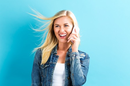 Young woman talking on the phone on a blue background Banque d'images
