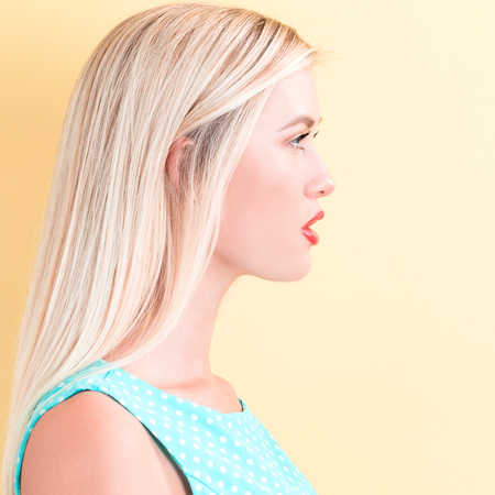 young woman face: Profile of a young woman on a yellow background