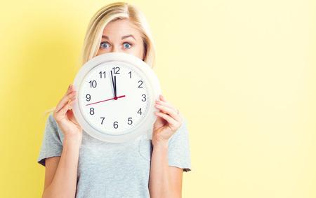 거의 12를 보여주는 시계를 들고 젊은 여자