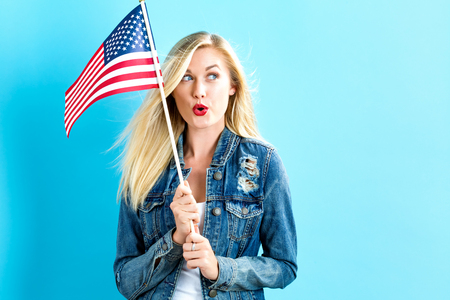 Happy young woman holding American flag Banco de Imagens