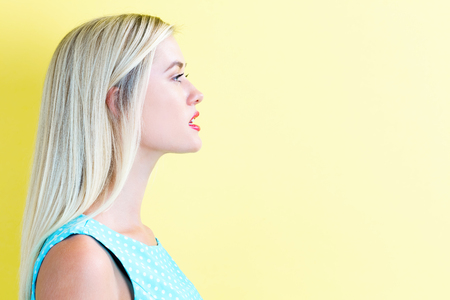 Profile of a young woman on a yellow background